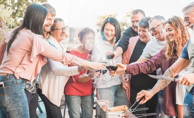 Familie die vlees roostert en met rode wijn bij bbq maaltijd openlucht toejuicht