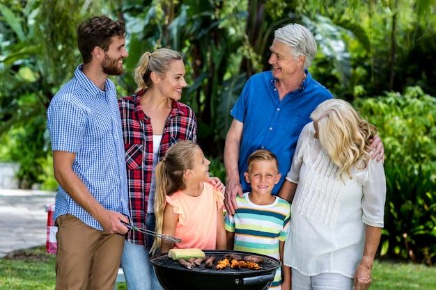 Familie die voedsel in barbecue roostert bij werf