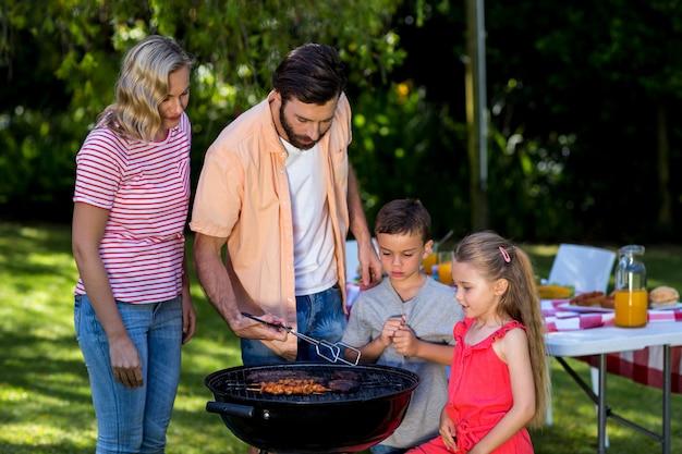 Familie die voedsel roostert bij barbecue in werf