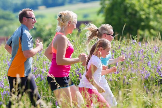 Familie die voor betere geschiktheid in de zomer loopt