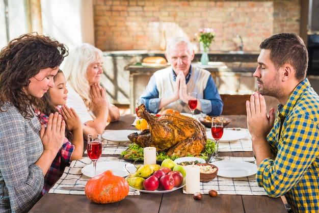 Familie die vóór maaltijd bidden
