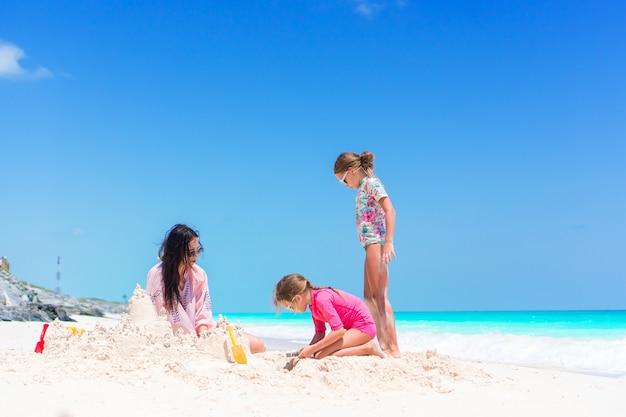 Familie die zandkasteel maakt bij tropisch wit strand. moeder en twee meisjes die met zand op tropisch strand spelen