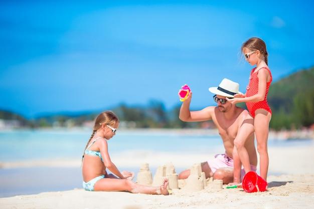 Familie die zandkasteel maakt bij tropisch wit strand. vader en twee meisjes die met zand op tropisch strand spelen