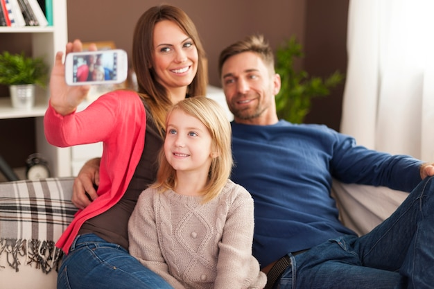 Familie die zelfportretfotografie neemt via de mobiele telefoon