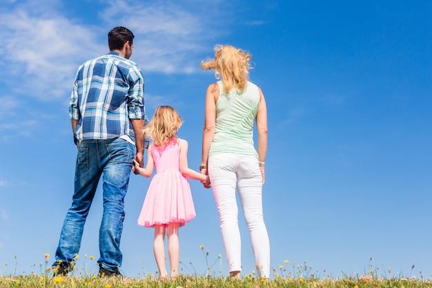 Familie die zich met hun ruggen aan de camera voor blauwe hemel bevindt