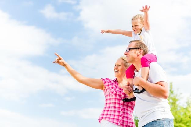 Familie die zomerwandeling op weide buitenshuis heeft
