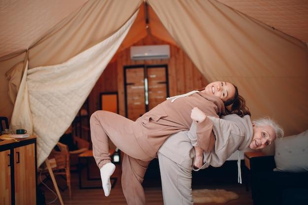 Familie doet oefeningen sport binnenshuis jonge en senior oudere vrouw ontspannen op glamping camping tent moeder en dochter modern bij fitness vakantie lifestyle concept