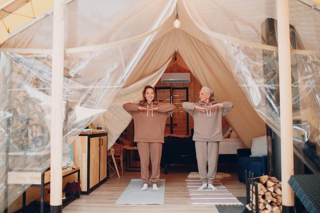 Familie doet oefeningen sport binnenshuis. jonge en senior oudere vrouw ontspannen op glamping camping tent. moeder en dochter modern bij het concept van de levensstijl van de fitnessvakantie.