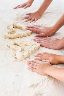 Familie, een jonge moeder met haar dochter en zoon, maakte in de keuken een hart van deeg.