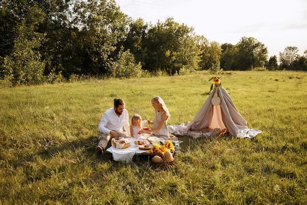 Familie eet op een picknick in de zomer