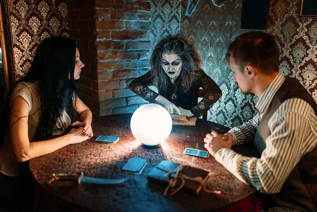 Familie en heks aan tafel met kristallen bol