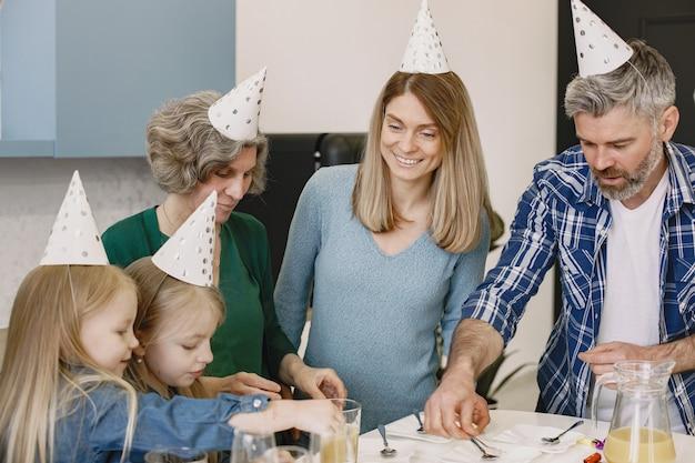 Familie en hun twee dochters vieren de verjaardag van oma's mensen gaan taart eten