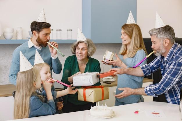 Familie en hun twee dochters vieren de verjaardag van oma's oude vrouw kreeg een cadeau
