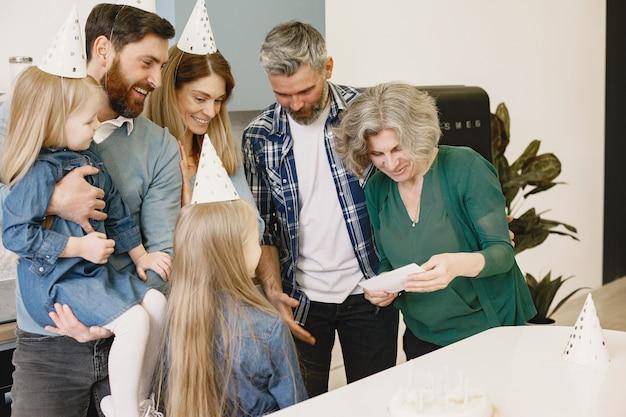 Familie en hun twee dochters vieren de verjaardag van oma's oude vrouw leest een kaart met wensen