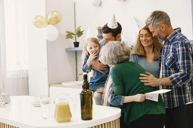 Familie en hun twee dochters vieren grootmoeders verjaardag klein meisje knuffelt haar grootmoeder