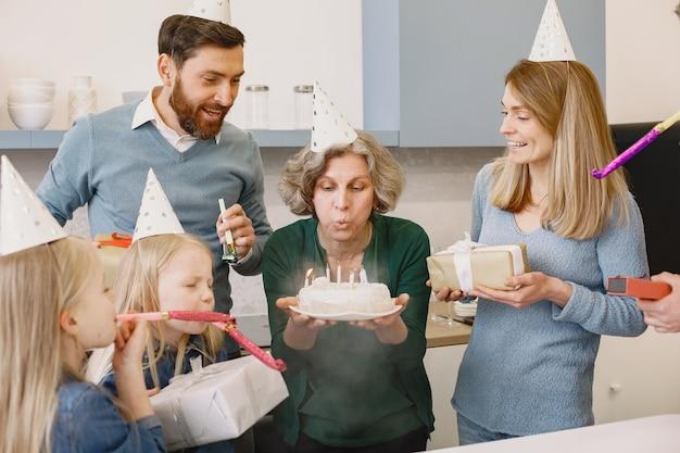 Familie en hun twee dochters vieren grootmoeders verjaardag oude vrouw blaast de kaarsjes uit