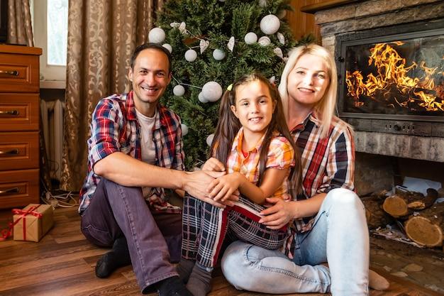 Familie en kerstboom in een oud houten huis