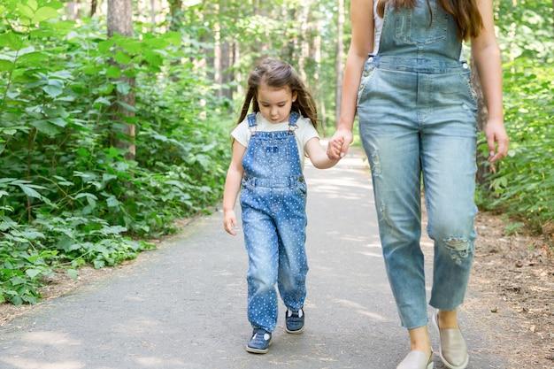 Familie en natuur concept portret van mooie vrouw en kind meisje wandelen in zomer park