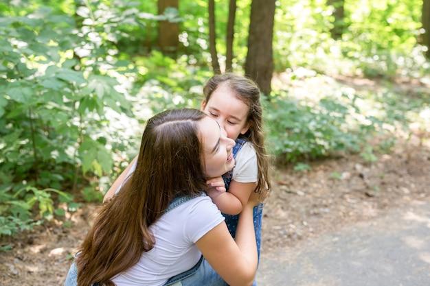 Familie- en natuurconcept - aantrekkelijke jonge vrouw veel plezier met haar dochtertje in het park