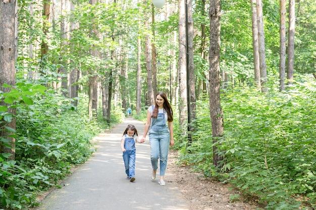 Familie- en natuurconcept - moeder en dochter brengen samen tijd buiten door.