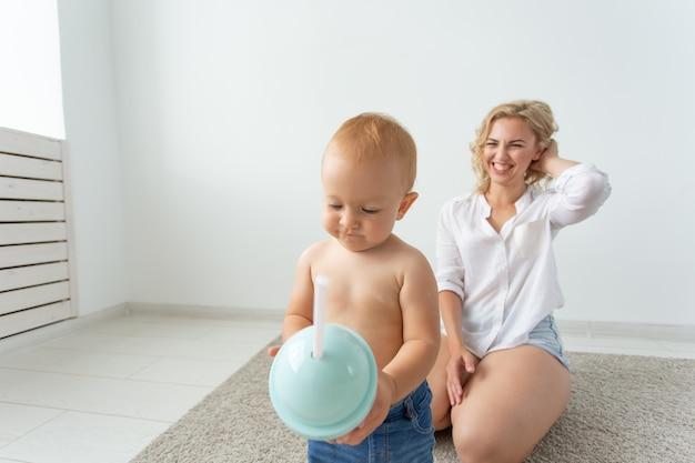 Familie en ouderschap concept schattige baby spelen met haar moeder op beige tapijt