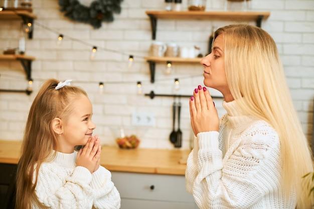 Familie en relaties concept. charmante jonge blonde moeder leert haar dochtertje trucs uit te voeren zittend aan het aanrecht met de handen ingedrukt, met taarten en koffie als toetje