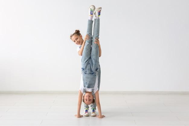 Familie en sport concept - twee acrobat tweelingmeisjes staan op de handen op een witte achtergrond.