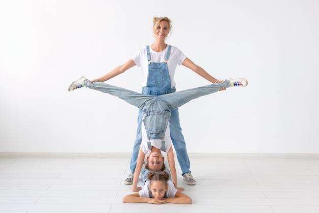 Familie en sportconcept - twee meisjes van de acrobaattweelingen aan het touw en hun moeder over witte muur.