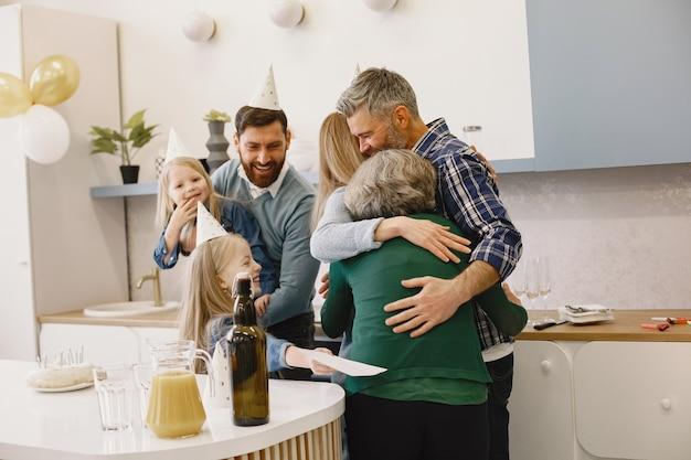 Familie en twee hun dochters vieren de verjaardag van grootmoeders volwassen zoon en dochter knuffelen zijn moeder