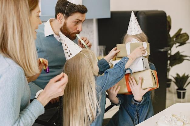 Familie en twee hun dochters vieren verjaardag in de keuken. mensen dragen een feestmuts. meisje houdt een doos met cadeautjes.