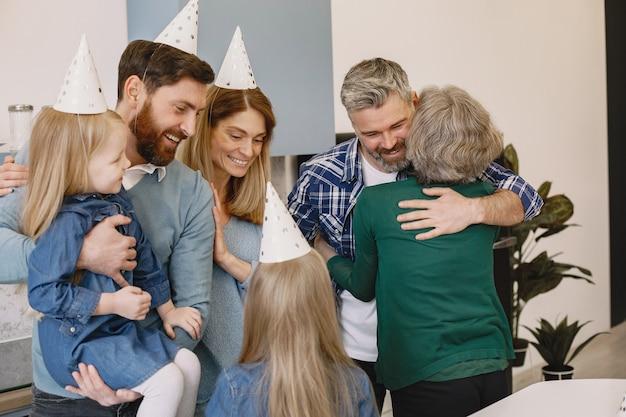 Familie en twee van hun dochters vieren de verjaardag van grootmoeders volwassen zoon knuffelt zijn moeder