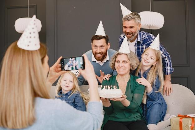 Familie en twee van hun dochters vieren verjaardag twee mannen en twee kleine meisjes zitten op een bank moeder maakt een foto van hen