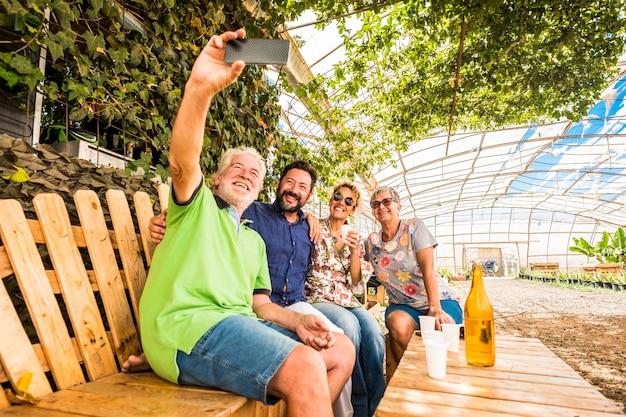 Familie en vrienden hebben samen plezier in vrijetijdsbesteding buitenshuis, ga zitten op een gerecyclede houten bank en maak een selfie met smartphone
