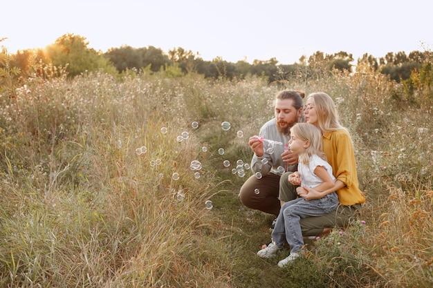 Familie en zeepbellen in de avond op een wandeling. gelukkige dikke familie brengt tijd samen door