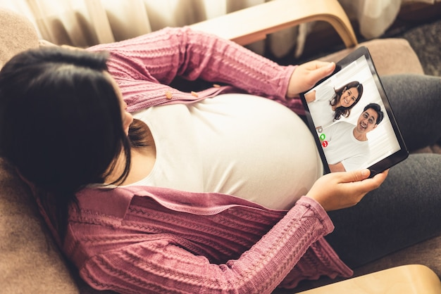 Familie en zwangere vrouw videobellen terwijl ze veilig thuis blijven tijdens covid-19