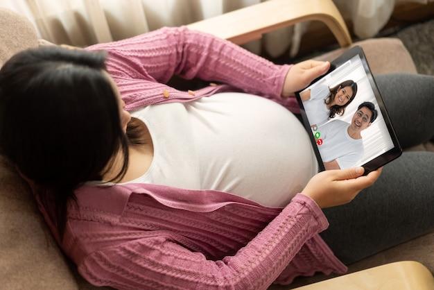 Familie en zwangere vrouw videogesprek terwijl ze veilig thuis blijven tijdens covid-19