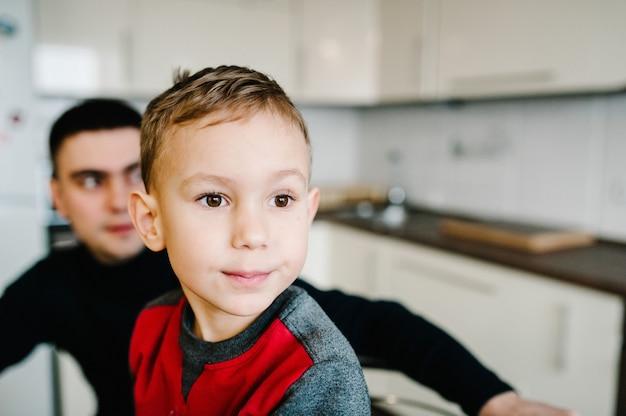 Familie, eten en mensen concept - gelukkige vader en zoon ontbijten in de keuken thuis.