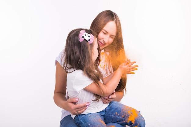 Familie, festival van holi en vakantieconcept - klein kindmeisje dat met haar moeder speelt die met verf wordt bedekt
