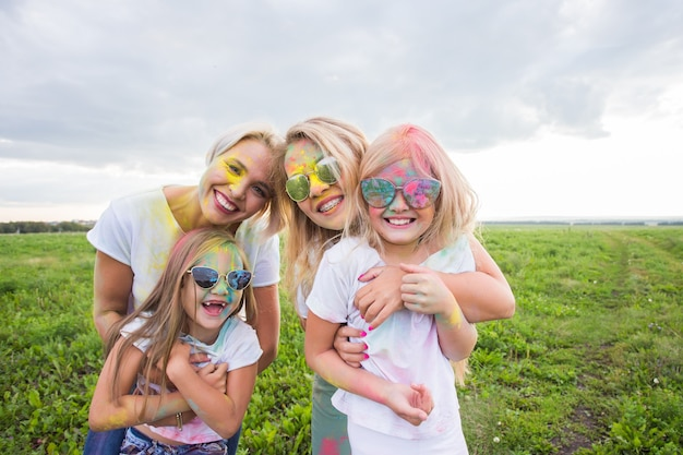 Familie, festival van holi en vakantieconcept - portret van gelukkige familie bedekt met verf