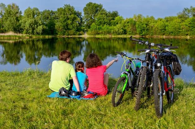 Familie fietstocht buitenshuis, actieve ouders en kind fietsen en ontspannen in de buurt van prachtige rivier