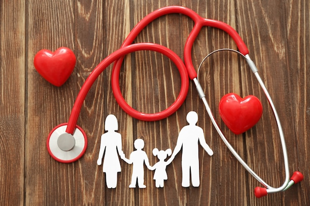 Familie figuur, rode harten en stethoscoop op houten tafel. zorgconcept