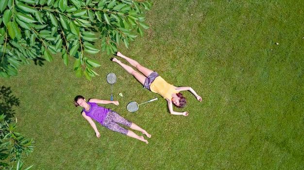 Familie fitness en sport buitenshuis, actieve moeder en dochter tiener badminton spelen in park, luchtfoto bovenaanzicht