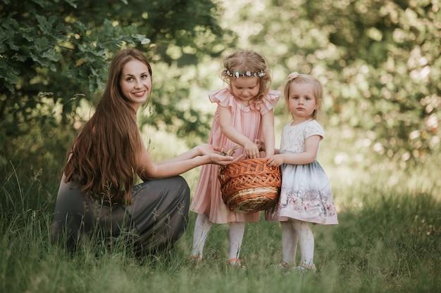 Familie foto moeder met dochters in het park. foto van jonge moeder met twee schattige kinderen buiten in de lente, mooie vrouw met dochter plezier