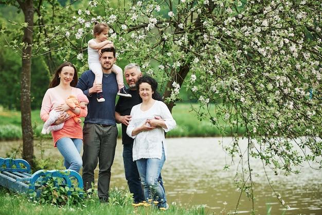 Familie foto. volledig lengteportret van vrolijke mensen die zich buiten samen dichtbij het meer bevinden