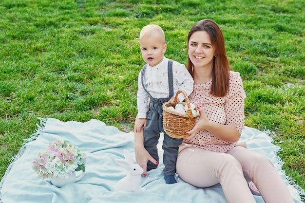 Familie fotosessie van moeder en zoontje voor pasen in het park, naast hen is een mand met eieren en een paashaas