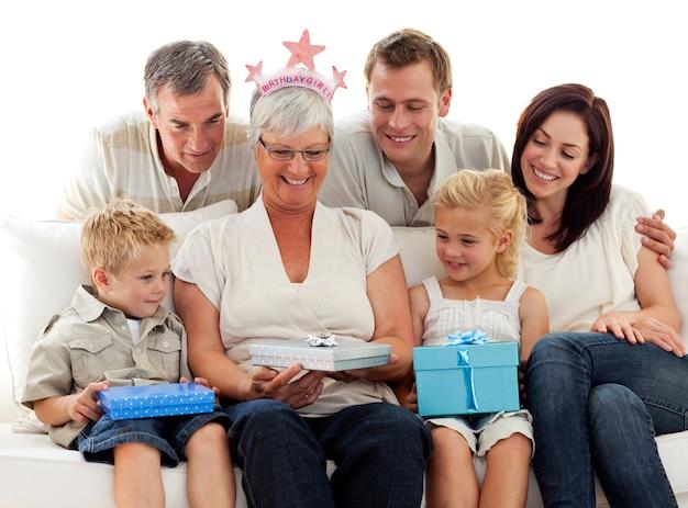 Familie geeft een cadeau aan grootmoeder voor haar verjaardag