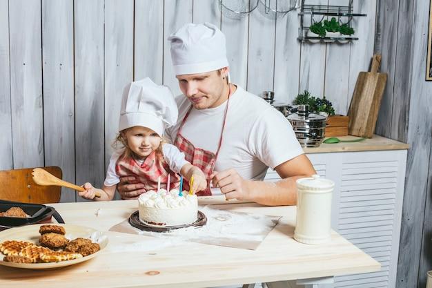 Familie, gelukkige dochter met mijn vader thuis in de keuken lachen en samen een verjaardagstaart bakken, met liefde