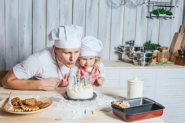 Familie, gelukkige dochter met mijn vader thuis in de keuken lachen en staken de kaarsjes op de verjaardagstaart aan