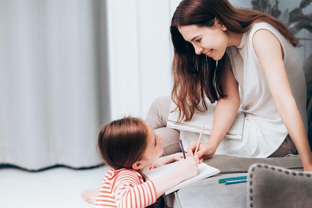 Familie gelukkige moeder lezen een boek en dochter tekenen samen