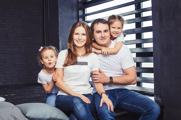 Familie gelukkige moeder, vader en twee meisjes tweelingzusjes thuis op de achtergrond van het raam.